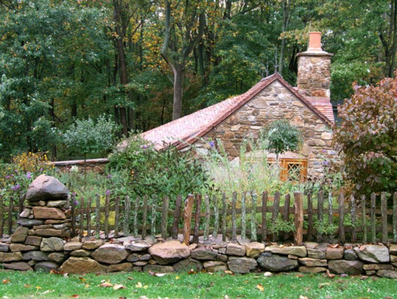 rustic picket fence around old stone home